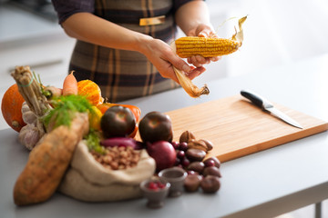 Closeup on young housewife peeling corn