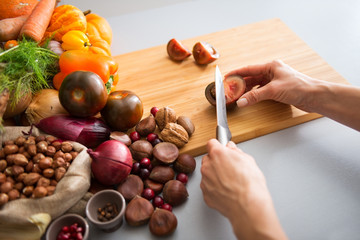 Closeup on young housewife cutting cherokee purple tomato