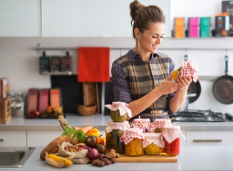 Happy young housewife with jars of pickled vegetables