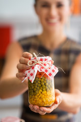 Closeup on young housewife showing jar with pickled vegetables
