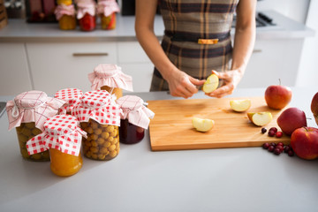 Closeup on young housewife cutting apple for jam
