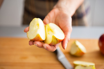 Closeup on young housewife showing apple slices