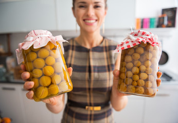 Closeup on young housewife showing jars with homemade compote