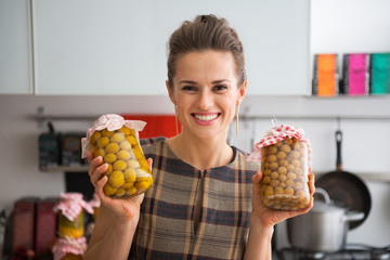 Portrait of happy young housewife showing jars