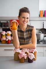 Housewife among jars with homemade fruits jam