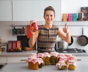 Portrait of happy young housewife among jars