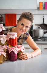 Portrait of happy young housewife looking out from jars