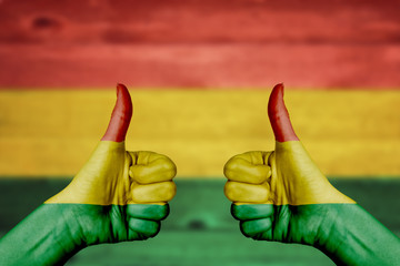 Bolivia flag painted on female hands thumbs up