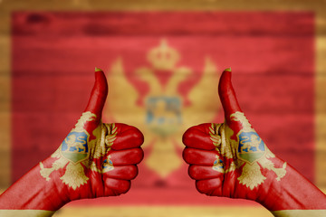 Montenegro flag painted on female hands thumbs up
