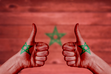 Morocco flag painted on female hands thumbs up