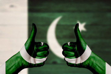 Pakistan flag painted on female hands thumbs up