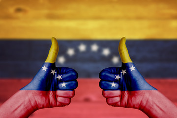 Venezuela flag painted on female hands thumbs up