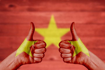 Vietnam flag painted on female hands thumbs up
