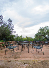 Empty cafe terrace exterior with chairs.
