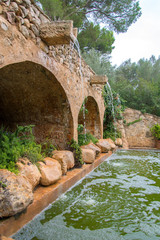 Portrait of medieval fountain with pond.