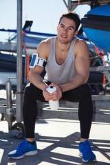 Cheerful athlete resting with bottle of water