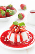 Vanilla panna cotta with strawberry sauce and nuts, vertical