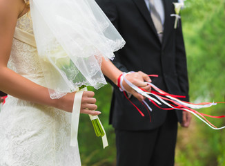 Hands newlyweds tied with a ribbon