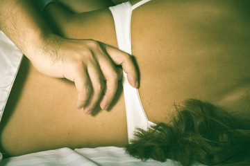 Male hand to doffed girl's bra