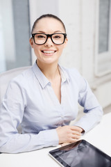smiling businesswoman in eyeglasses with tablet pc