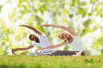 happy couple stretching and doing yoga exercises
