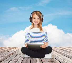 happy girl with headphones and tablet pc