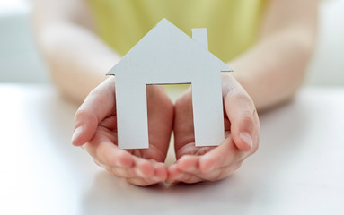 close up of happy girl hands holding paper house
