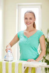 happy woman with iron and ironing board at home