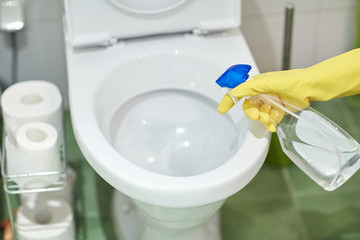 close up of hand with detergent cleaning toilet
