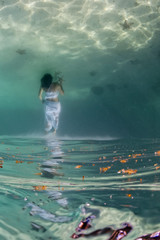 White dressed girl while swiming underwater