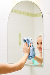 close up of happy woman cleaning mirror with rag