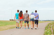 group of teenagers walking outdoors from back