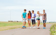 group of smiling teenagers with skateboards