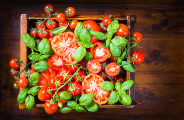 Tomatoes and basil.Italian food on rustic wood background.