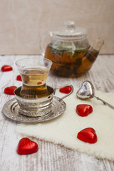 tea in a glass with a coaster and candies