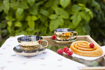 cups of tea and bun with raspberry