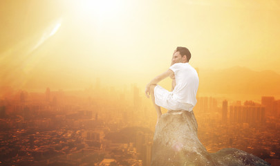 Man sitting on a rock overlooking a city