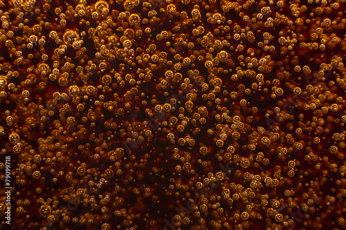Macro black bubbles on glass wall of cola rise up - 79099718