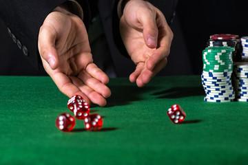 Male hand rolling five dice on green felt