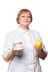 Dentist with denture for demonstration and apple