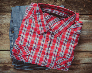Plaid shirt and pair of jeans on wooden background. Top view. Vi