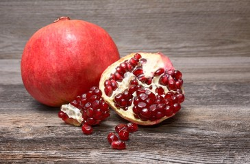 Red juicy pomegranate, on dark rustic wooden table
