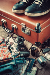Old travel suitcase, sneakers, clothing, map, filmstrip and retr