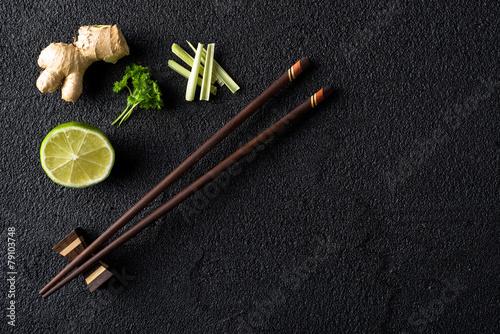 Chopsticks i karmowi składniki na czerń kamienia stołowym odgórnym widoku
