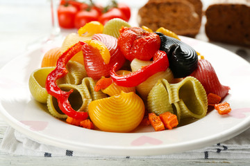 Tasty multicolor pasta with pepper, carrot and tomatoes