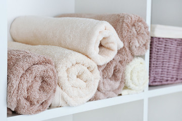 Rolled towels with wicker basket on shelf of rack background