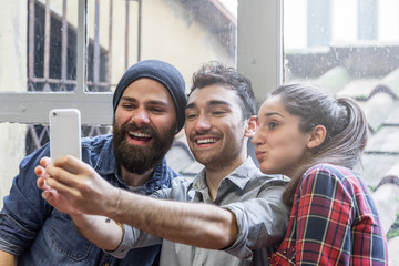 Three friends take a Selfie with phone