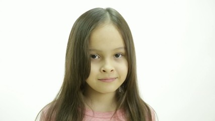 Young girl in pink top looking up and then glancing sideways