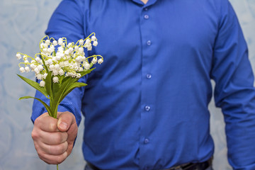 Man holding lilies of valley. Gift on March 8