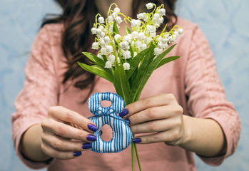 Gift on March 8. Girl holding lily of valley